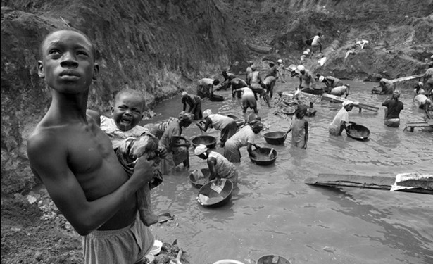 Slaves pan for gold in Accra, Ghana. Many have children with them as they wade in water poisoned by mercury that's used in the extraction process. (CC Lisa Kristine NC)